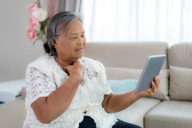 elder Asian woman talking with doctor on ipad