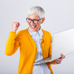 older woman in yellow sweater celebrating success while holding her laptop