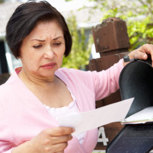 Older Asian woman opening mail with bad news