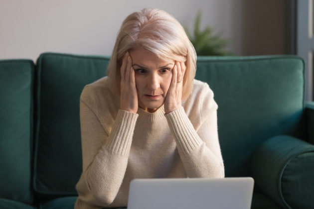 Shocked mature woman feeling stressed reading unbelievable online news