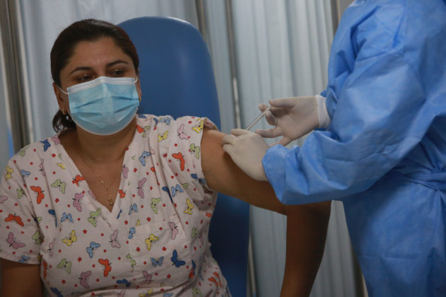 masked woman receiving covid vaccine