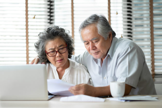 Elderly Asian couple looking at a bill with computer open and puzzled expressions.