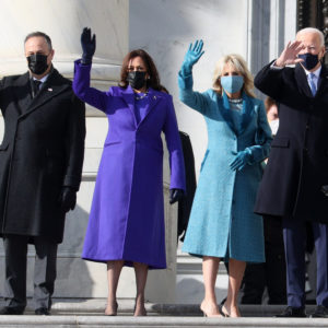 Kamala and Doug Harris and Jill and Joe Biden standing and waving on inauguration day