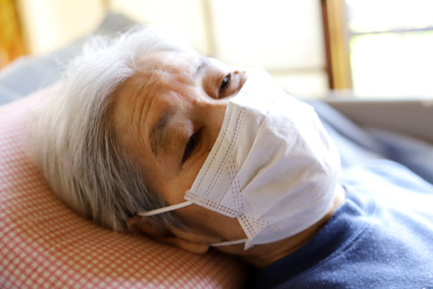 asian elder woman laying in hospital bed with mask on