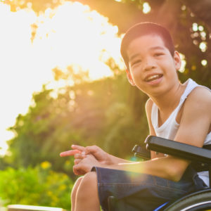 young Asian boy in wheelchair smiling while outside with setting sun glow