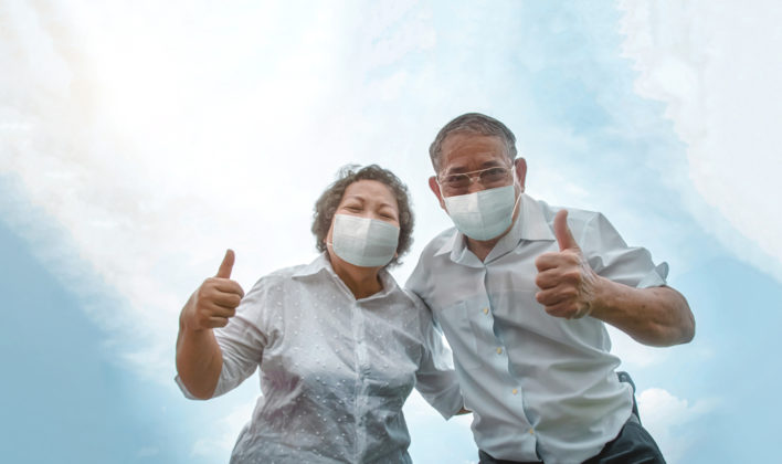 older Asian couple outside with masks on giving a thumbs up. Sky in background