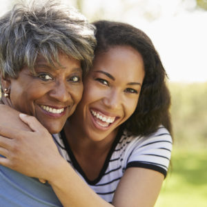 Older Black woman and daughter smiling and hugging outsideei
