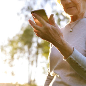 Elderly woman is holding a phone in a sunny park. Be careful on the Internet, fraud