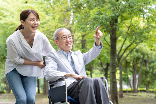 young asian woman and old asian man with wheelchair in park