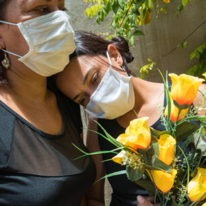 Mother and daughter mourning those lost to the coronavirus, wearing face masks, showing mutual support, hugging