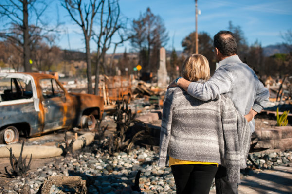 Man and his wife owners, checking burned and ruined house and yard after fire