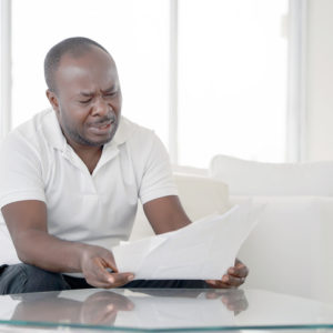 Man reads negative news in a letter at home on the couch.