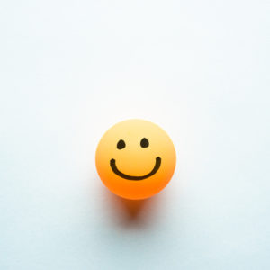 Happy smiley emoticon on a yellow ping pong ball with space for text blue background