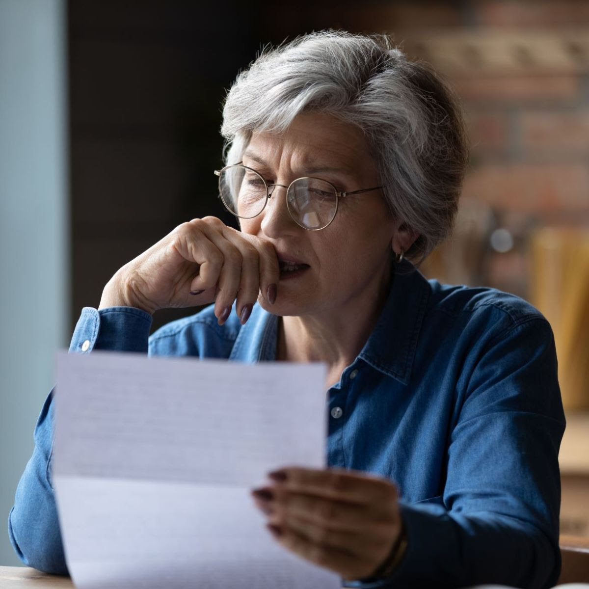 older woman looking concerned while sitting and reading a letter from the mail