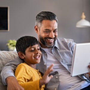Father and son using digital tablet to make a video call